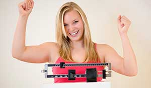 woman weighing herself - weight loss center